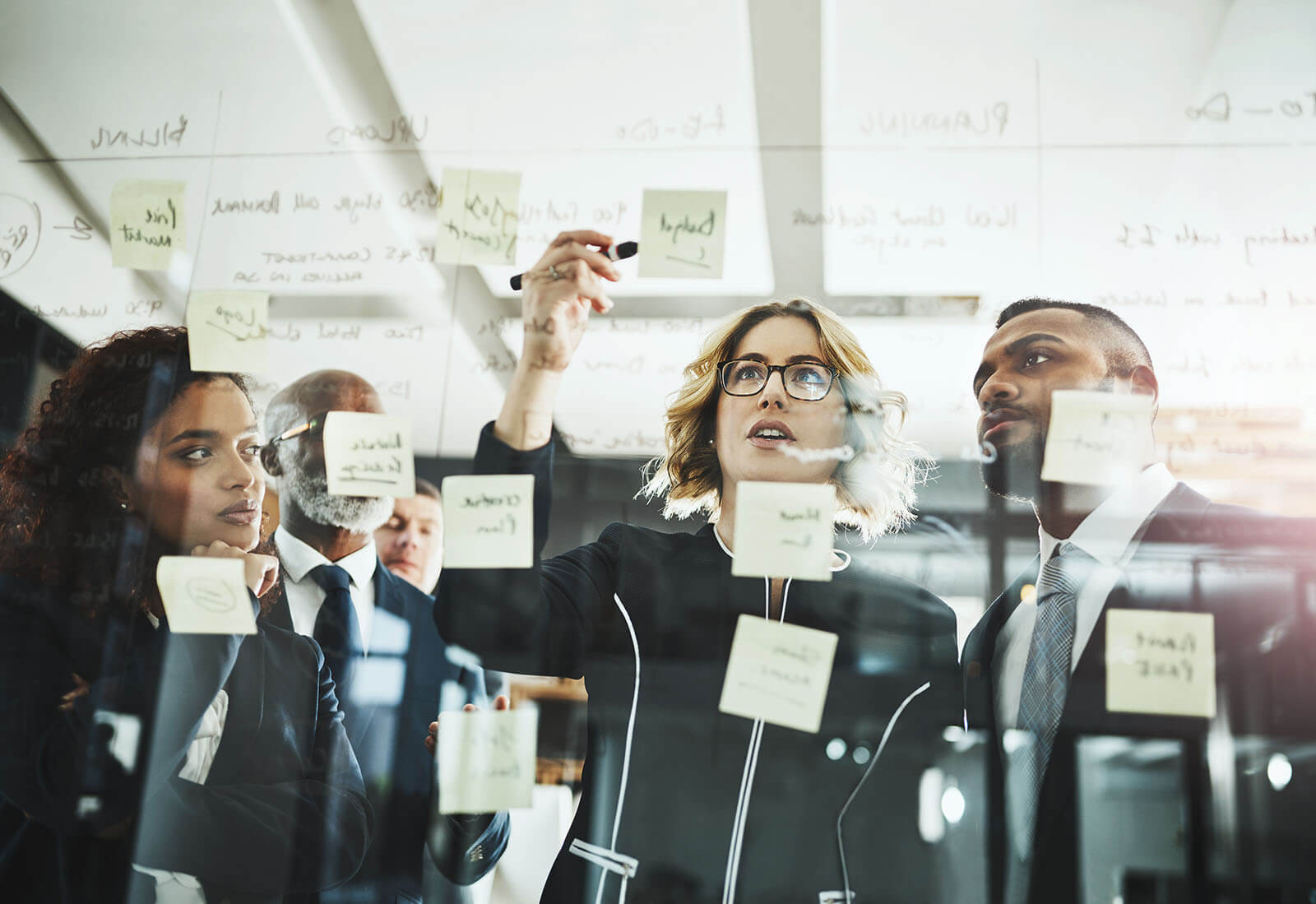 Business people writing on a glass wall and note pad