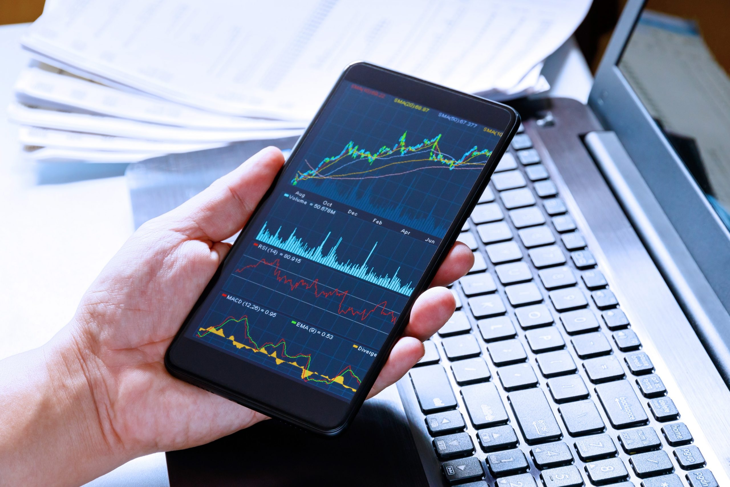 A person views various graphs on their smartphone while working on their laptop.