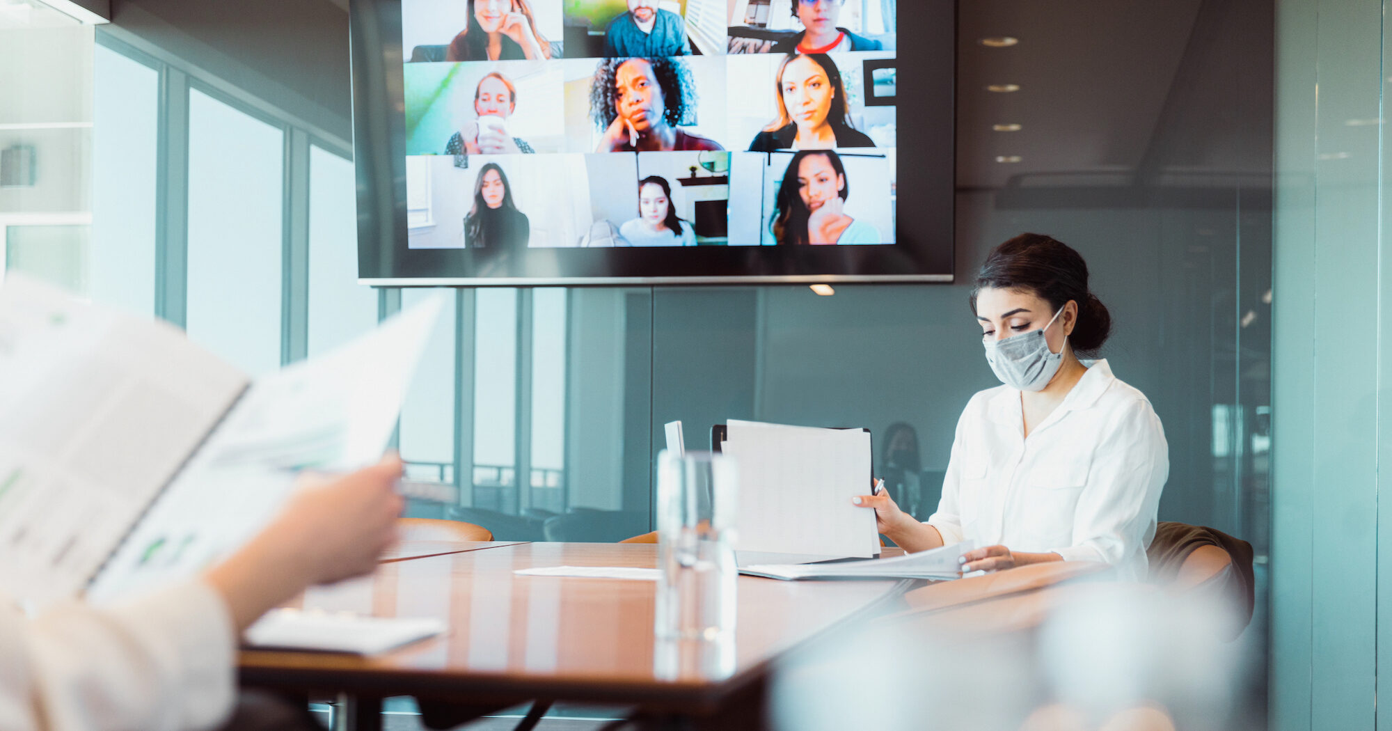People at a conference table wearing masks with a videoconference in the background