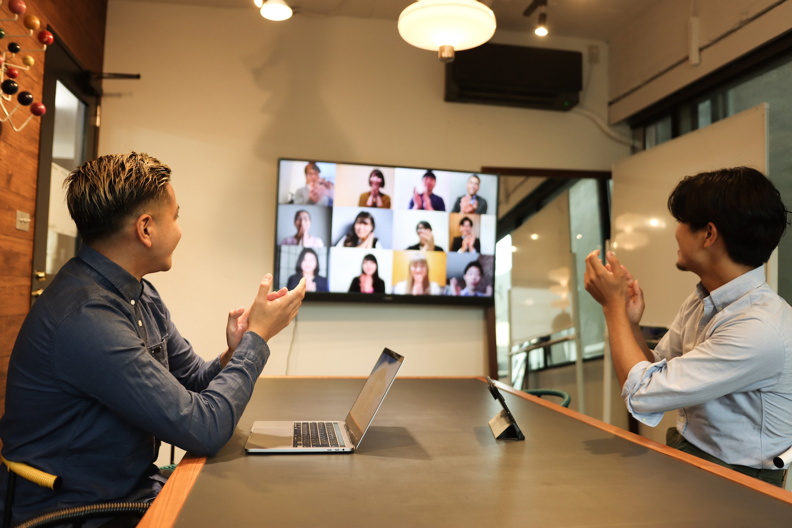 Employees at a conference table interacting with a videoconference
