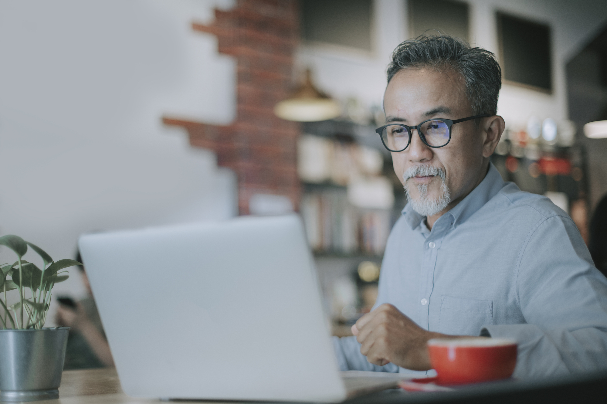 Man seated in front of computer with a cuppa